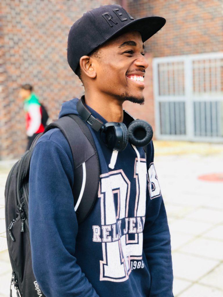 Man Wears Black Cap Blue Hoodie And Backpack At The School 2826131